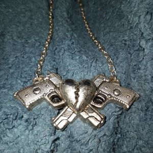 A necklace with 2 guns and a heart by rock rebel